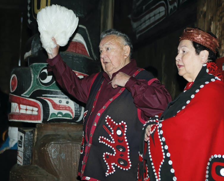 The keeper of hundreds of Kwakwaka'wakw songs, Kwaksistalla Wathl'thla (Clan Chief Adam Dick), chanting at a feast (qui'las) with Mayanilh (Dr. Daisy Sewid-Smith).